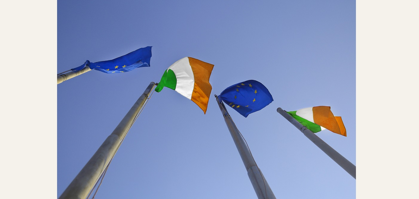 Ireland and EU flags seen from below against a blue sky