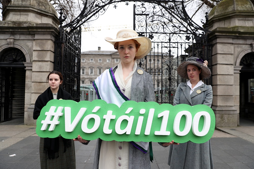"""Suffragettes"" outside Leinster House displaying the Vótáil100 hashtag"